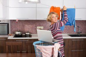 室内で洗濯物を干す女性