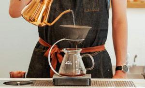 コーヒーをドリップするためお湯を注ぐ男性